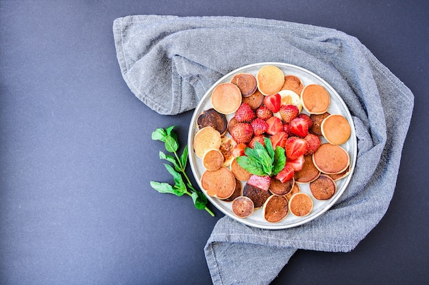 Plate with traditional pancakes and tiny pancake cereal with strawberries and mint leaves . trendy food. mini cereal pancakes