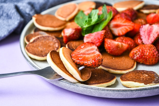 Plate with traditional pancakes and tiny pancake cereal with strawberries and mint leaves . trendy food. selective focus on fork with tiny pancakes and strawberry