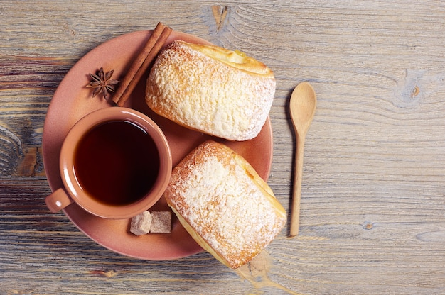 Plate with two fresh buns and cup of hot tea on rustic wooden table, top view