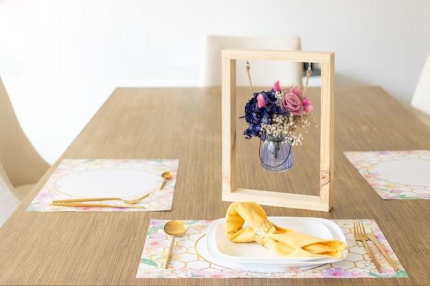 小さなフラワーアレンジメントで飾られたテーブルの上に、道具を置いたプレート
