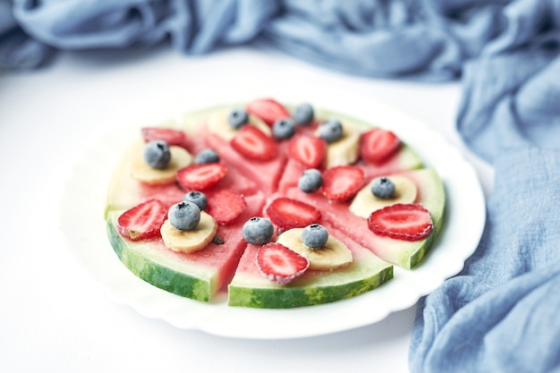 Plate with vegan slices of frozen fruits: arbuk, blueberries, blueberries, banana with yogurt