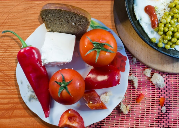 A plate with vegetables, bread and feta cheese near a frying pan with breakfast on a wooden background.