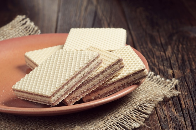 Plate with wafers on dark wooden table