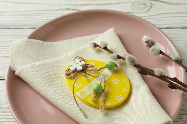 Тарелка с деревянным пасхальным яйцом, кухонной салфеткой и сережками на деревянном фоне