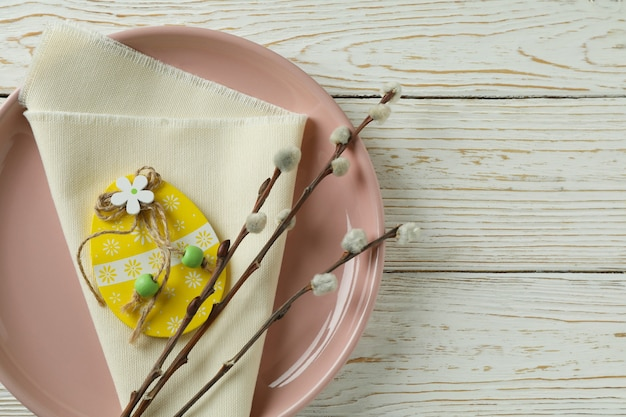 Plate with wooden easter egg, kitchen napkin and catkins on wooden background