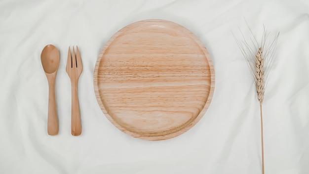 Тарелка деревянная, ложка деревянная и вилка деревянная с сухим цветком ячменя на белой ткани. вид сверху сервировки стола на белом фоне