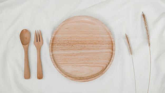 Тарелка деревянная, ложка деревянная и вилка деревянная с сухим цветком щетинистого лисохвоста на белой ткани. вид сверху сервировки стола на белом фоне