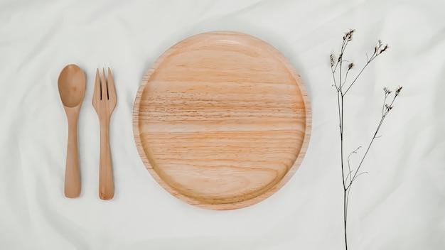 Тарелка деревянная, ложка деревянная и вилка деревянная с сухим цветком limonium на белой ткани. вид сверху сервировки стола на белом фоне