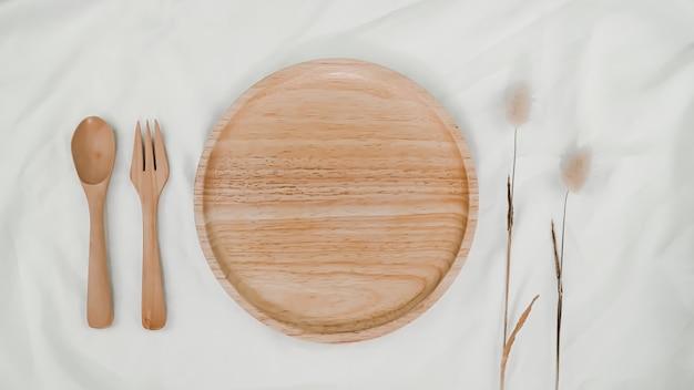 Тарелка деревянная, ложка деревянная и вилка деревянная с сухим цветком хвост кролика на белой ткани. вид сверху сервировки стола на белом фоне