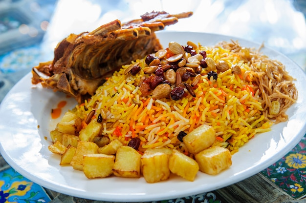 Plate of yellow rice topped with mutton meat and potatoes.