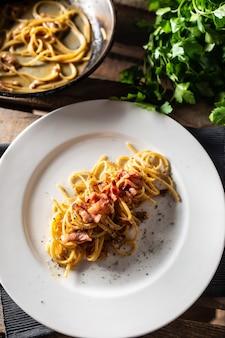 Итальянские спагетти карбонара на тарелке с ветчиной сверху.