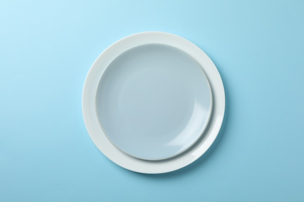 Plates on blue background, top view and space for text