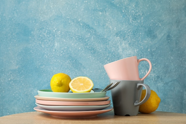 Plates and cups with lemons stacked on wooden table