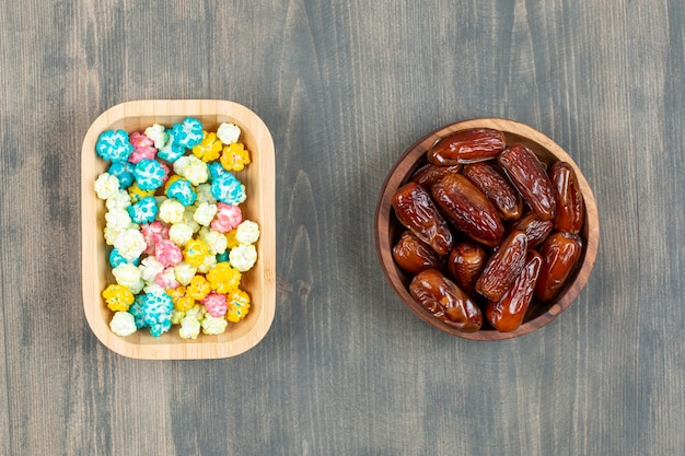 Plates of dates and colorful popcorns on wooden surface