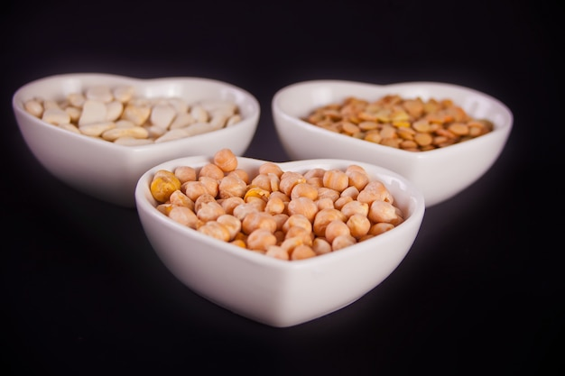 A plates of dry beans, peas and chickpeas on black background.