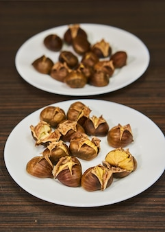 Plates filled with baked edible chestnuts on a wooden surface