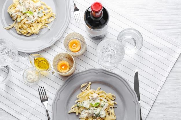 Тарелки вкусной пасты альфредо с курицей на сервированном столе
