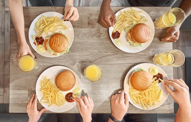 Тарелки с гамбургерами, картофель фри, сок стаканы на столе.