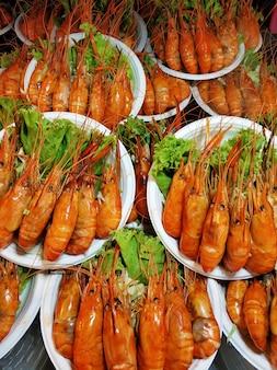 길거리 음식 시장에서 거대한 삶은 새우 접시.