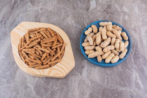 Тарелки арахиса и крекеров на мраморной поверхности. фото высокого качества
