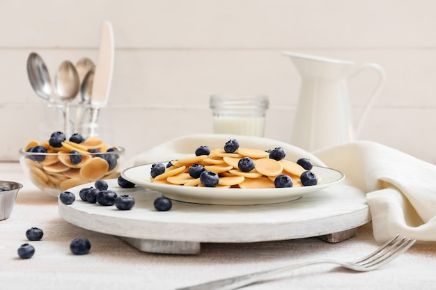 Тарелки вкусных блинов со свежей черникой на светлой поверхности
