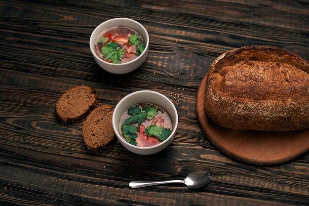 Тарелки томатного супа и хлеба на деревянной доске