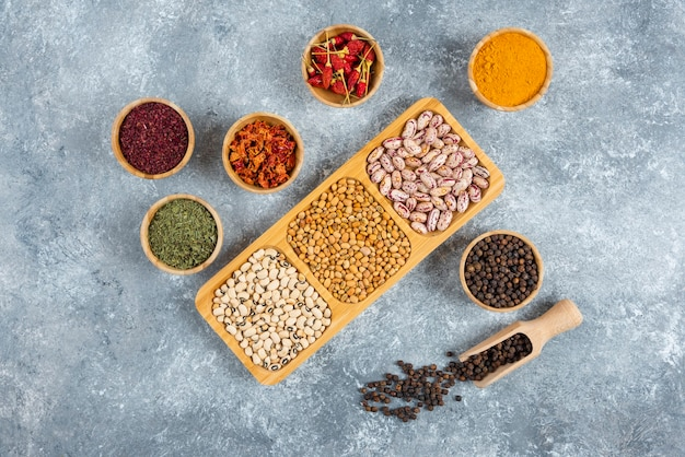 Plates of raw beans and spices on marble background.