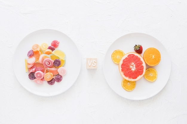 Plates of sweet candies versus fruits over white texture rough background
