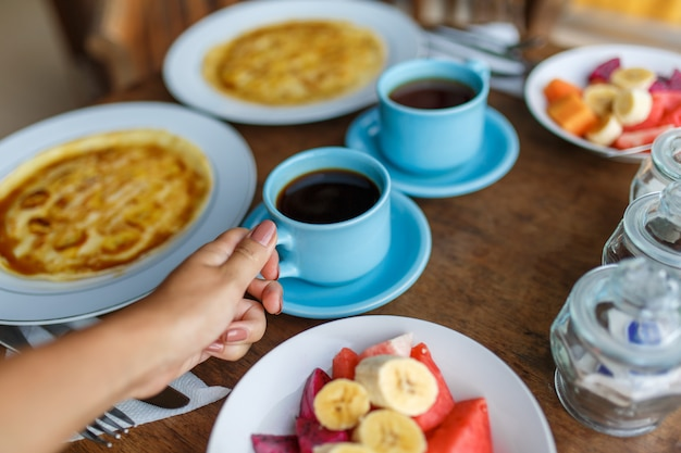 Plates with banana pancakes tropical fruits and two cups of coffee on wooden table