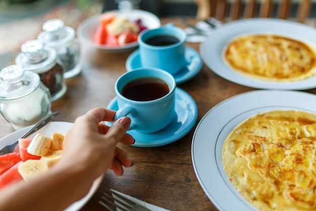 Plates with banana pancakes, tropical fruits and two cups of coffee on wooden table.