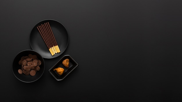Plates with chocolate sticks on a dark background