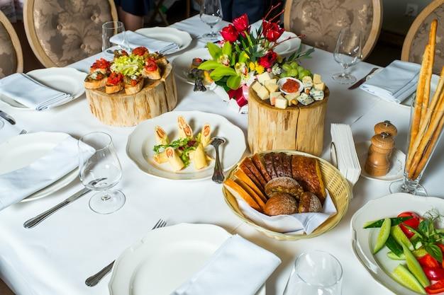 Тарелки с холодными закусками и нарезанным сыром на сервировочном столе