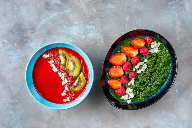 Plates with colorful strawberry and spinach smoothies seeing from above