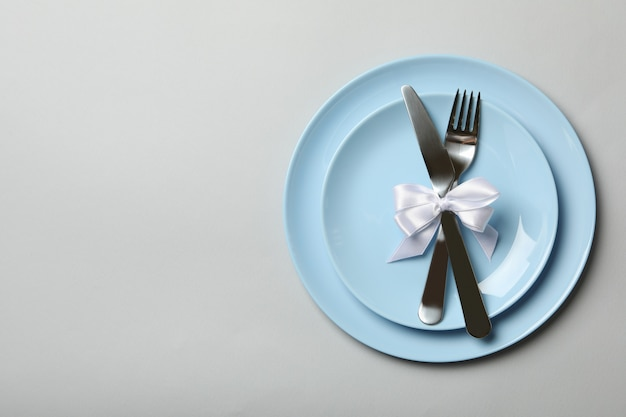 Plates with cutlery and bow on white background