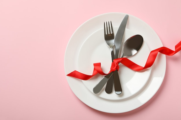 Plates with cutlery and red bow on pink background