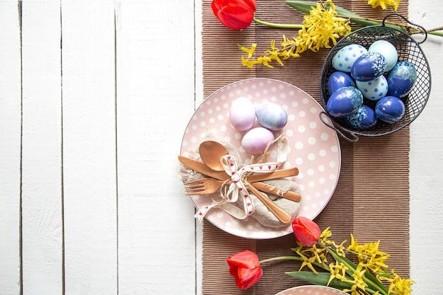 Тарелки с куличом, цветами и пасхальными яйцами. сервировка стола для космоса экземпляра праздника пасхи.