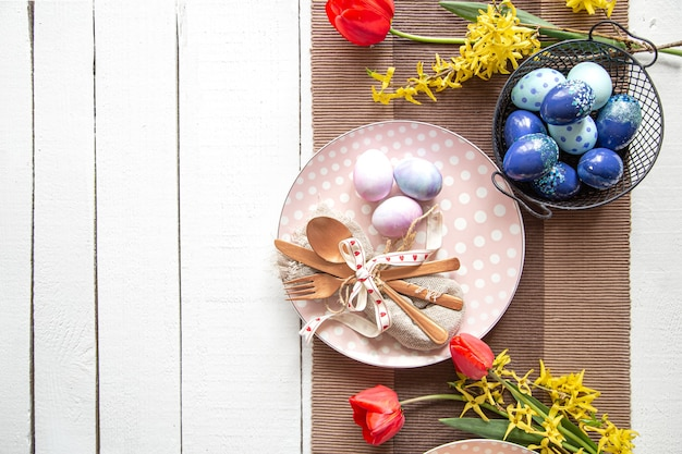 Plates with easter cake, flowers and easter eggs. table setting for the easter holiday copy space.