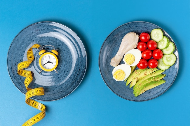 Plates with food and alarm clock on a blue background, intermittent fasting concept.