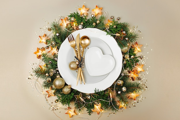 Plates with gold cutlery on christmas decoration background. flat lay, top view.