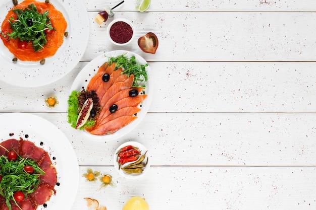 Тарелки с копченой рыбой и мясом