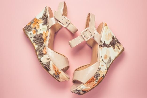 ピンクの背景にベージュのパテントレザーの厚底サンダル。レトロなスタイル、ファッション。女性の夏の靴。