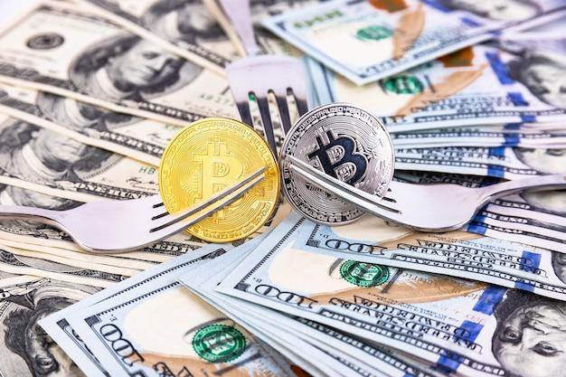 100ドル札とカトラリーを背景にしたプラチナとゴールドのビットコイン。