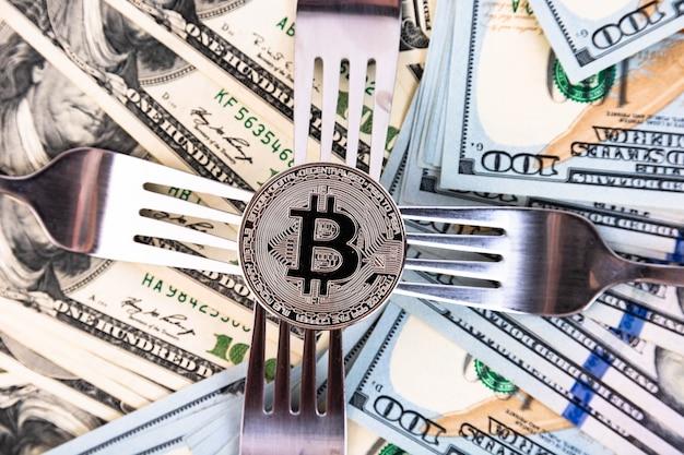 Платиновый биткойн на фоне стодолларовых банкнот и столовых приборов.