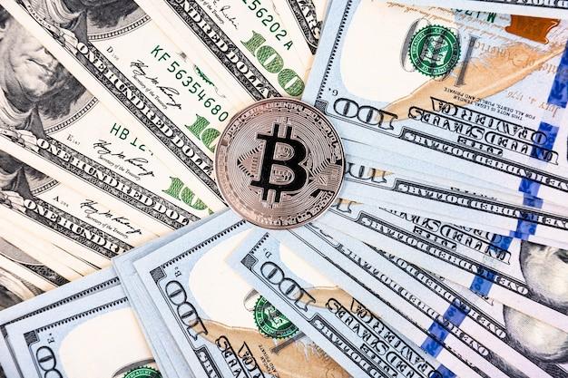 Платиновый биткойн на фоне стодолларовых купюр
