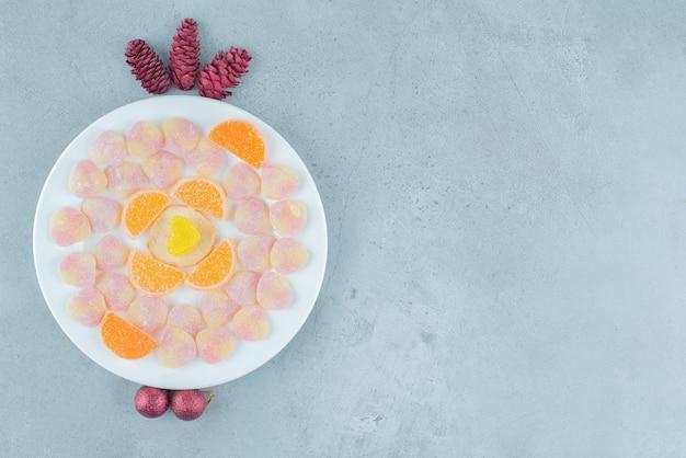 Piatto di marmellate assortite, con pigne e palline su marmo.