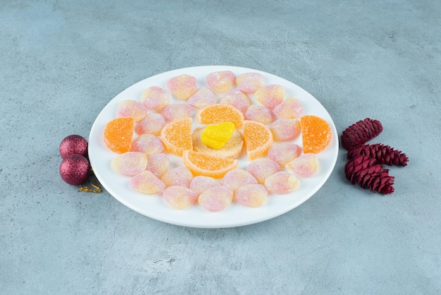 Platter of assorted marmelades, with pine cones and baubles on marble.