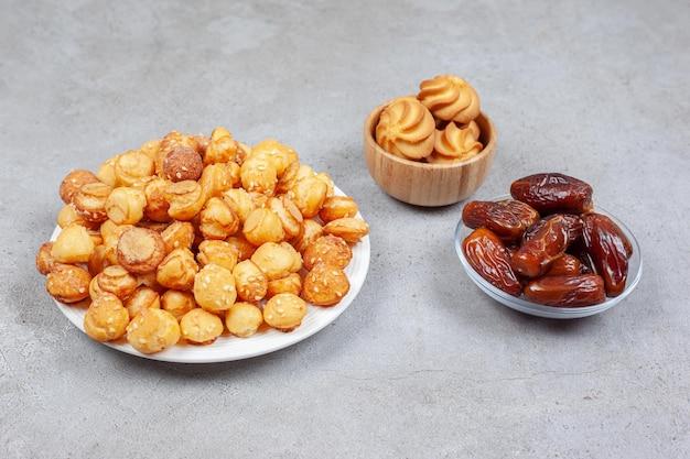 Piatto e ciotola piena di patatine fritte e un piccolo mucchio di datteri su fondo di marmo. foto di alta qualità
