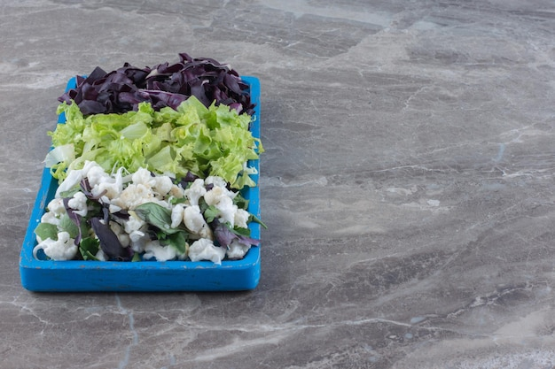 Platter of chopped cabbage, cauliflower and amaranth on marble surface
