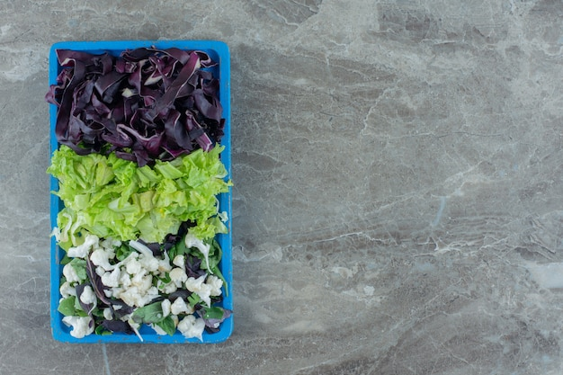 Platter of chopped cabbage, cauliflower and amaranth on marble.