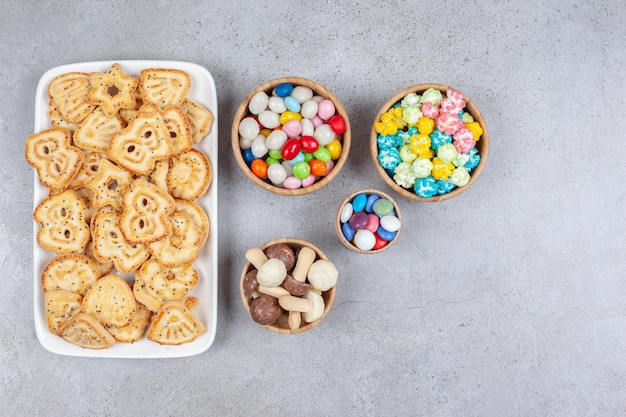 A platter of cookie chips next to bowls of candies and chocolate mushrooms on marble surface